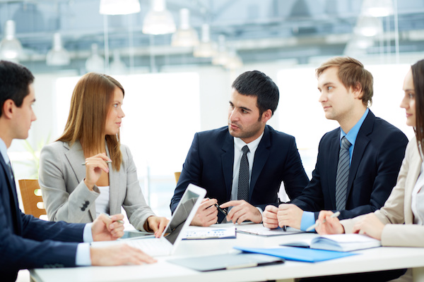 mage of business partners listening to female employee at meeting
