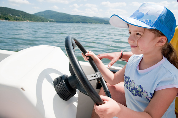 little girl driving a boat