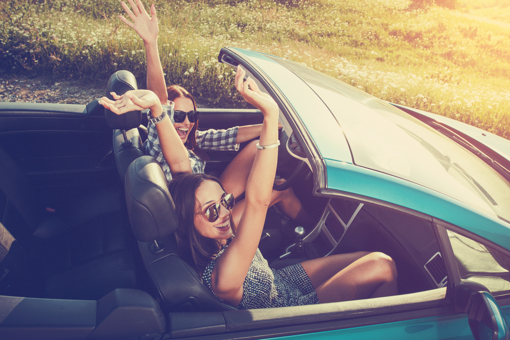 two girls driving in a convertible
